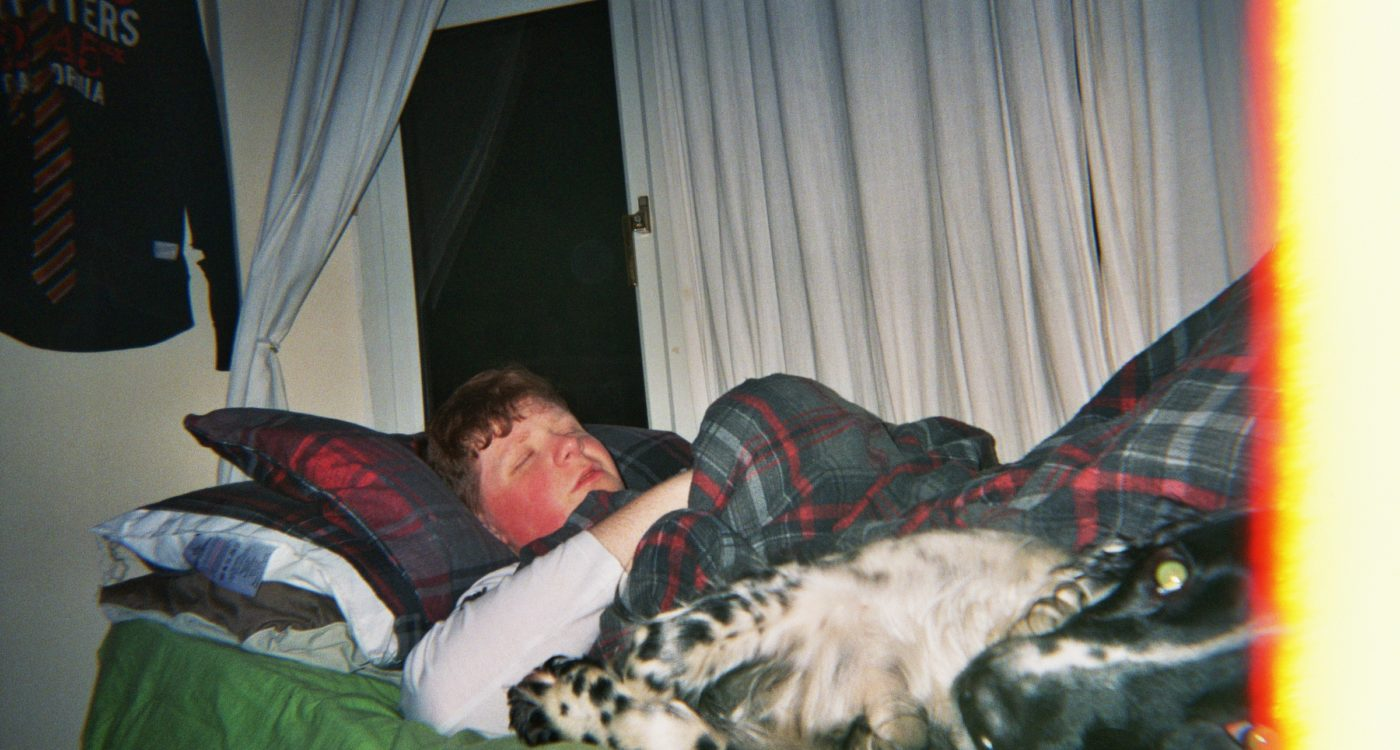Fred's photograph (for the 21st Century Kids) of his brother asleep in bed. There is a dog also on the bed looking a the camera in the foreground.