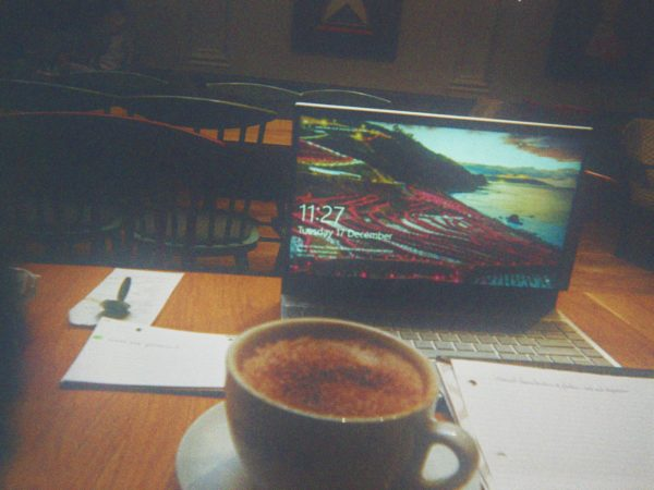 Lydia's photograph (for the 21st Century Kids) of table in coffee shop with open laptop, cup of what looks like coffee or hot chocolate and paper with notes