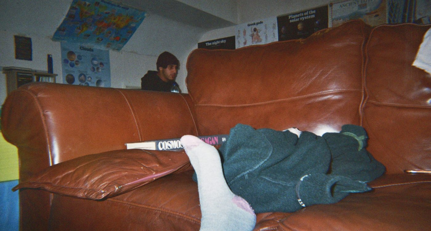 Beatriz's photograph (for the 21st Century Kids) of her friend in the background behind the sofa with is at the foreground of the image. Beatriz's foot is resting on the sofa.
