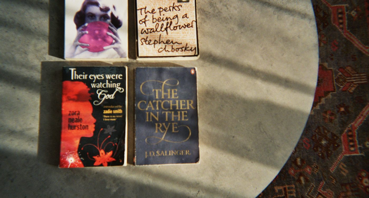 Abbi's photograph (for the 21st Century Kids) of four books, [The Catcher in the Rye by J.D Salinger, The Perks of Being a Wallflower by Stephen Chbosky, Their eyes were watching god by Zora Neale Hurston and a book by Sylvia Plath, The title of the book isn't shown]