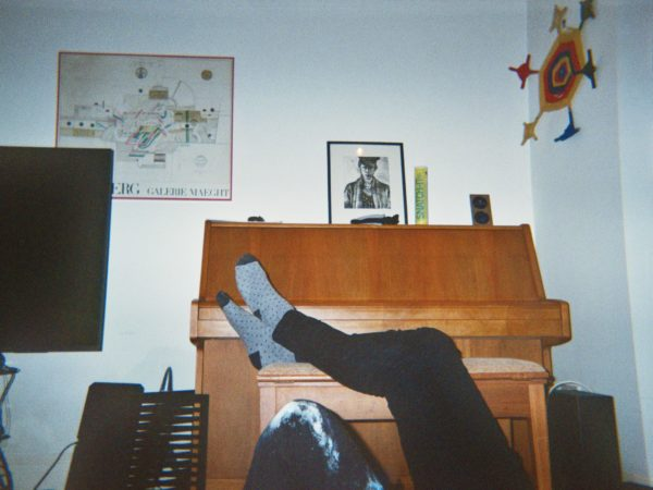 Elio's photograph (for the 21st Century Kids) of a room with a TV, pictures on the wall, and a piano. Someones legs are resting on the piano bench.