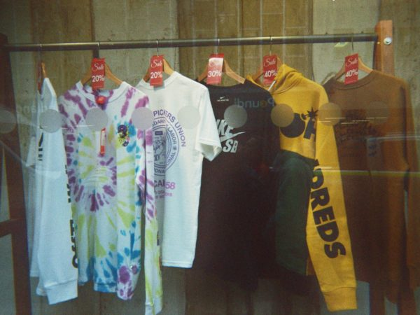 Brooke's disposable photograph (for the 21st Century Kids) of a shop front with a range of T-shirts and hoodies on a rail.