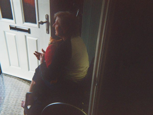 Damien's photograph (for the 21st Century Kids) of his mum. She is sitting in her wheelchair looking outside the front door a dog in her lap.