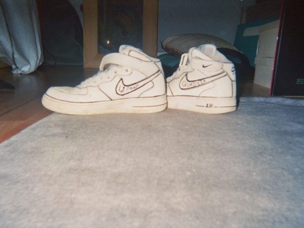 Brooke's photograph (for the 21st Century Kids) of Nike trainers with black ink drawn over the nike ticks