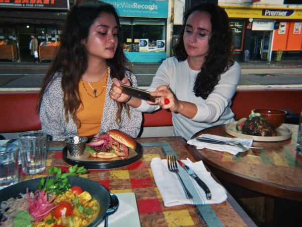 Beatriz's photograph (for the 21st Century Kids) of her sister and her mum at the restaurant Turtle Bay. They are sitting at the table with their meal and her mum is taking a picture of the burger whilst her sister watches her.