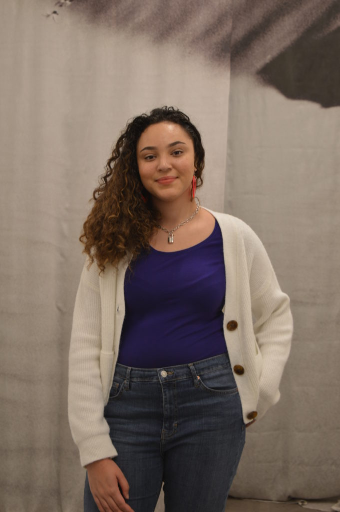 Photograph of Abbi for the 21st Century Kids Project. She is standing inside the Arnolfini, Bristol. The background appears to be a black and white curtain. She is standing and smiling. She is wearing a purple top, white cardigan and blue jeans.