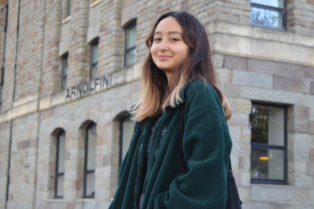 Photograph of Beatriz for the 21st Century Kid project. She is standing outside the Arnolfini in Bristol. She is looking into the camera and smiling. She is wearing a forest green fleece jacket and has a black tote bag over her shoulder.