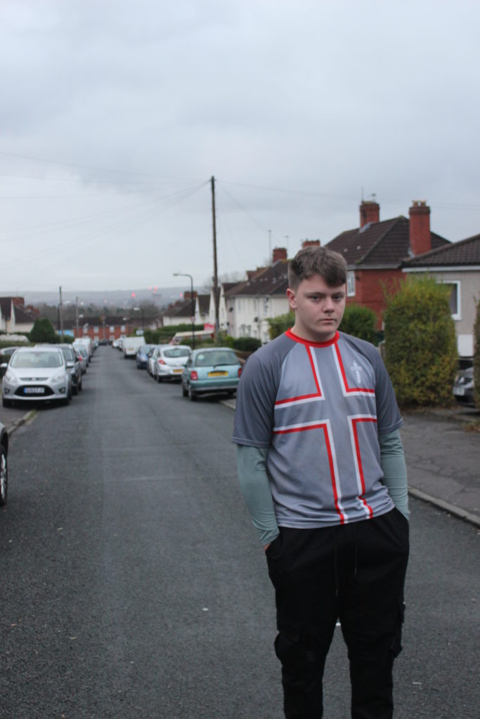 Photograph of Damien for the 21st Century Kids project. He is standing in the road in Lockleaze, Bristol. There are cars parked either side of the road and houses in the background. Damien is wearing a grey top with the St Georges cross on it and black jogging trousers