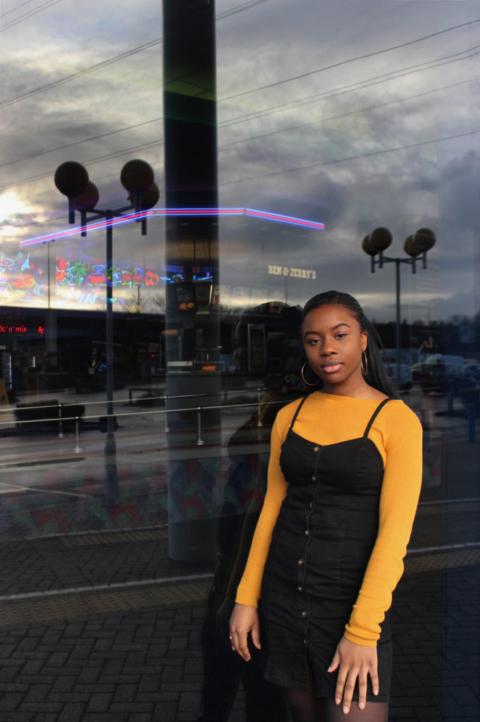 Photograph of Lydia for the 21st Century Kids project. She is beside the Showcase cinema in Avonmeads, Bristol. She is standing in front of a window. The food counter inside the cinema is just visible and the car park is reflected. She is wearing a yellow/ mustard top and black dress.