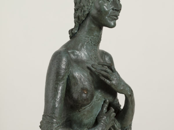 A bronze sculpture of a smiling naked woman shown from the waist up, with hands raised, one across her stomach and the other in front of her left breast.