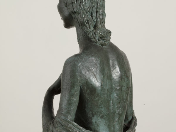 A rear view of a bronze sculpture of a naked woman shown from the waist up, showing an elaborate knotted hair style.