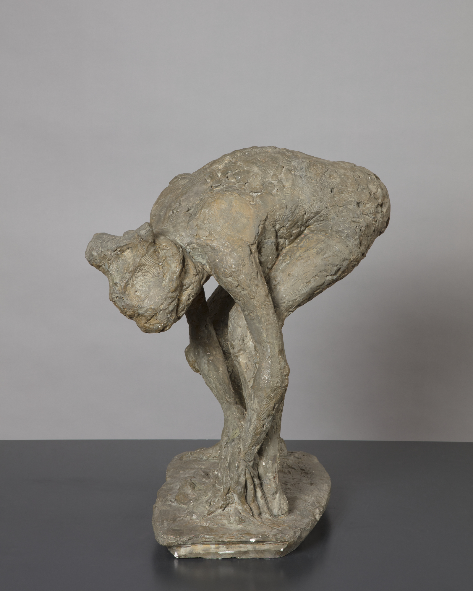 A sculpture of a naked woman bending forward drying her left foot with a towel that is held in both hands