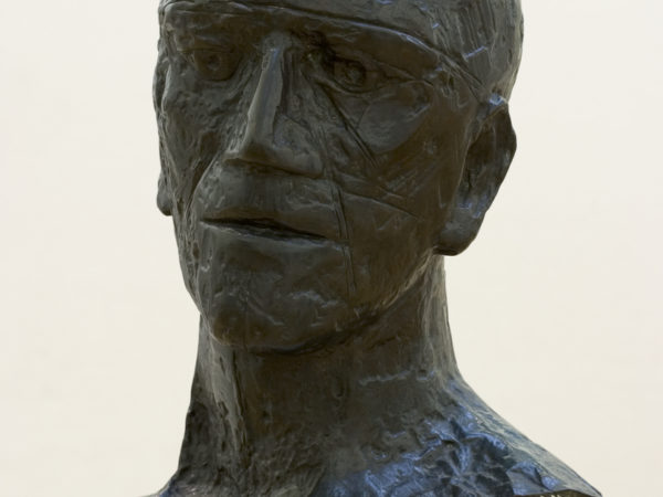 Bronze sculpture of the head and neck of a bald-headed man facing foward. His wide mouth is thin-lipped and his eyes appear to stare into the distance.