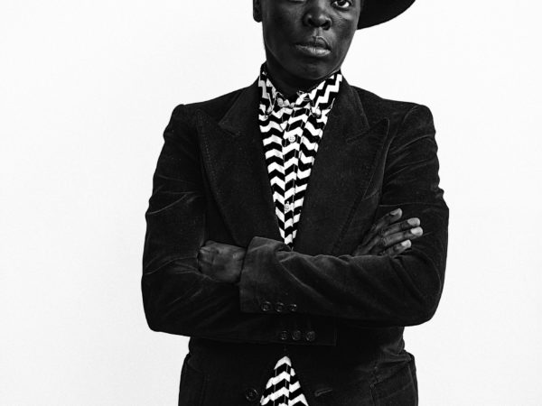A black and white photographic self-portrait Zanele Muholi from the hips upwards with arms folded across the chest, shown wearing a hat at a jaunty angle, jeans, a black velvet jacket, and a black and white zig-zagged patterned shirt.