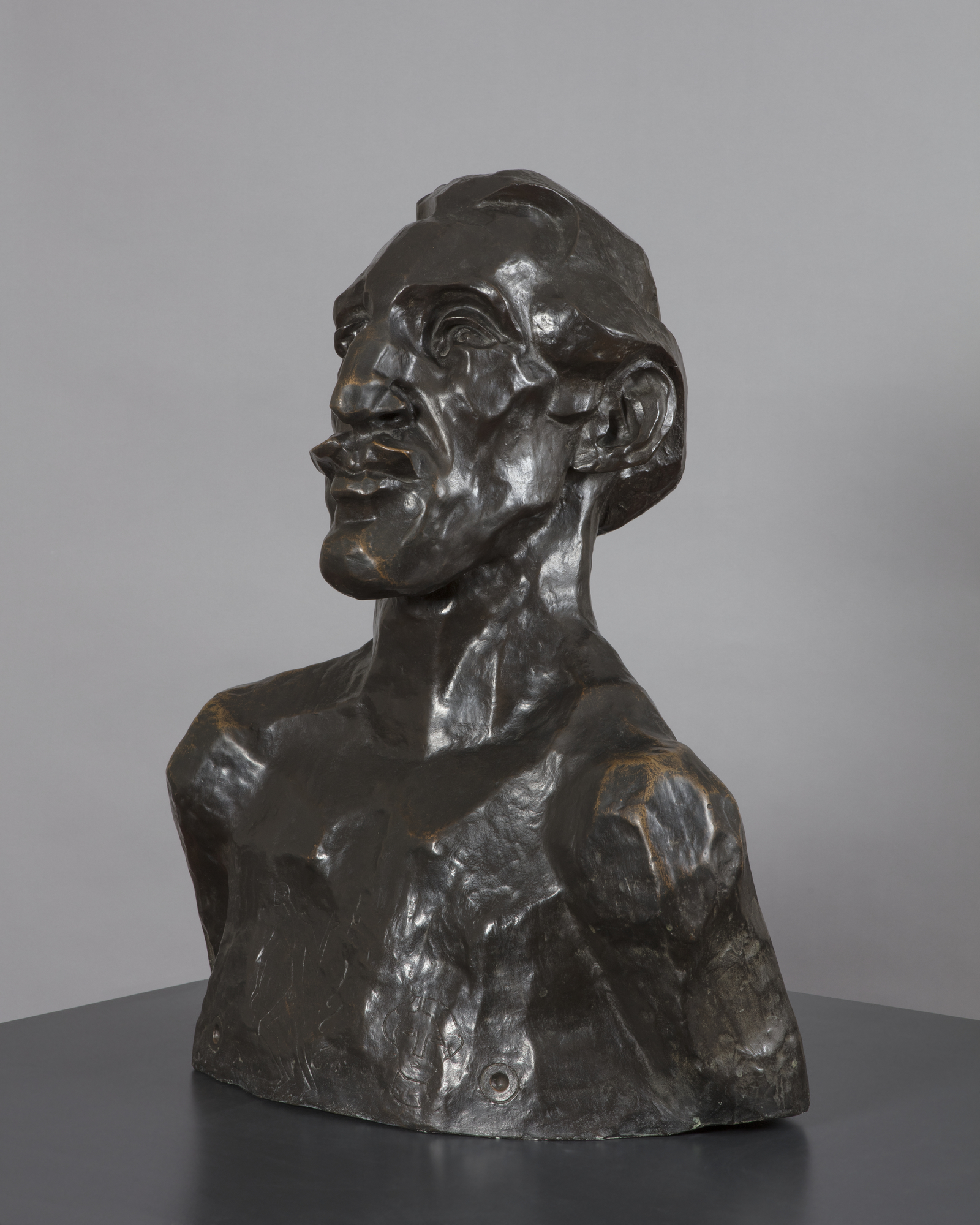 A bronze sculpture of a naked man's head and shoulders, viewed facing half-right , with an angular face and prounced chin, nose and lips as well as a short swept back receding hair style. His bare chest has been scratched to represent a tattooed design.