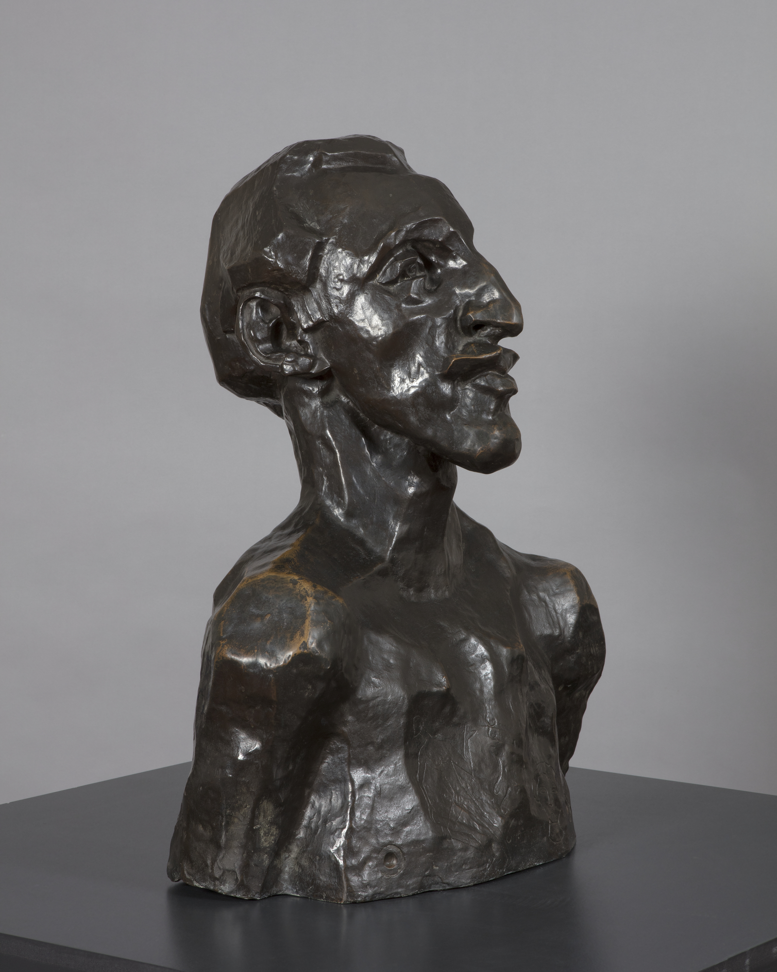 A bronze sculpture of a naked man's head and shoulders, viewed facing half-left, with an angular face and prounced chin, nose and lips as well as a short swept back receding hair style. His bare chest has been scratched to represent a tattooed design.