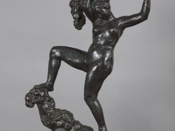 A bronze sculpture of a naked woman balancing on a rocky peak with her right leg held high and bent at the knee. Her arms are raised above her head holding a vine with bunches of grapes.