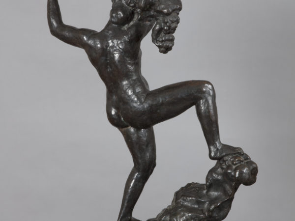 A rear view of a bronze sculpture of a naked woman balancing on a rocky peak with her right leg held high and bent at the knee. Her arms are raised above her head holding a vine with bunches of grapes.