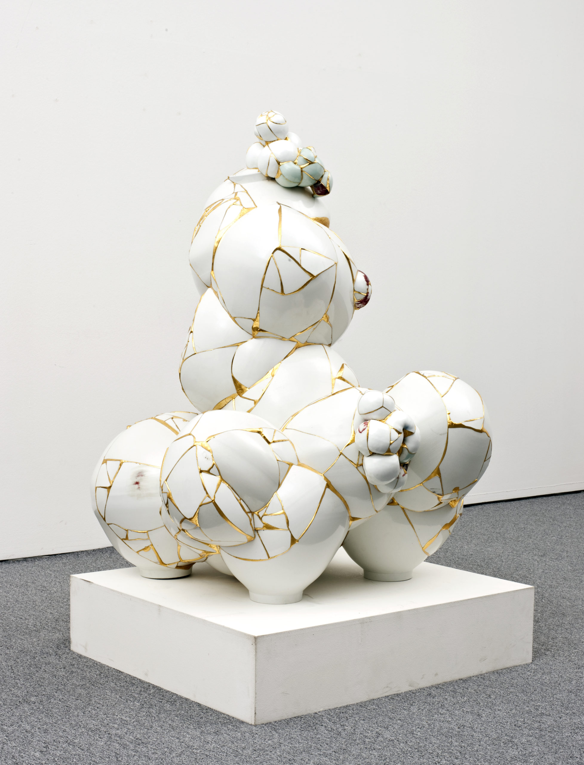A sculpture made of a series of broken porcelain sherds fused together with gold leaf to create a series of irregular spherical shapes resembling bubbles joined together.
