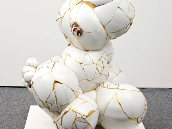 A sculpture made of a series of broken porcelain sherds fused together with gold leaf to create a series of irregular spherical shapes resembling bubbles.joined together.