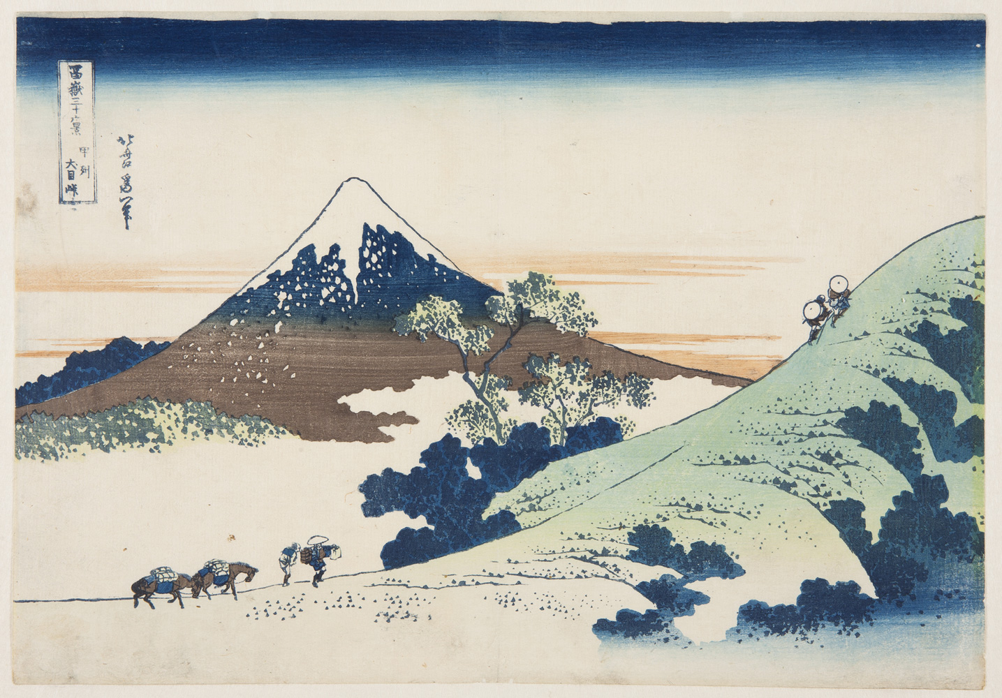 Japanese print of Inume Pass in Kai Province. Travellers with horses climb the hill in the foreground. Mount Fuji rises up in the background.
