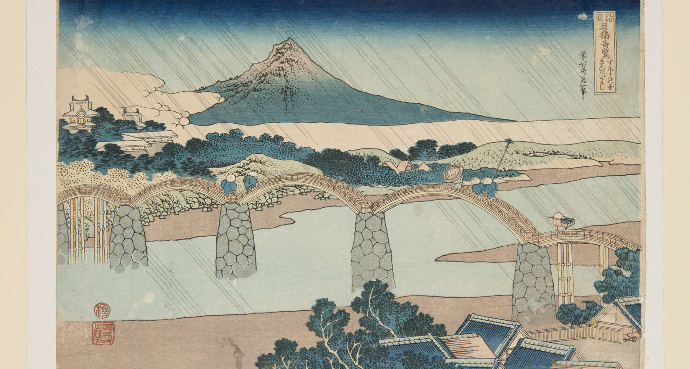 Japanese print of a landscape. Rain slants across the scene top left to bottom right. In the foreground there is a river bank with trees and roof tops. Middle is a bridge spanning the river with five arches and people standing on it. In the background there are a few buildings, trees, fields and an imposing mountain.