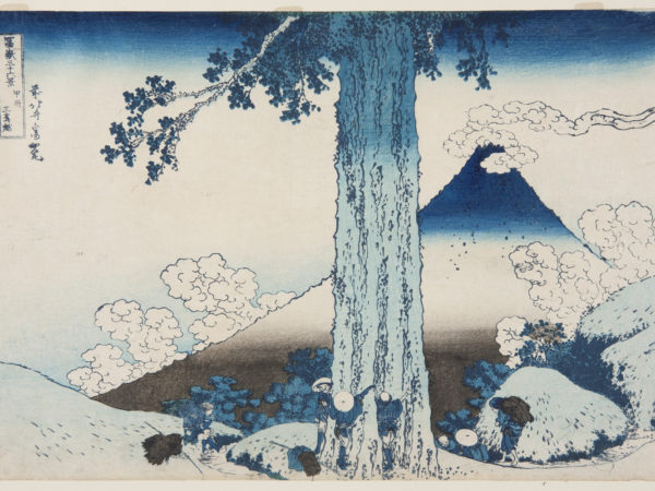 Japanese landscape. A trunk of a large tree in the centre with a group of people, in traditional dress, surrounding it having laid their packs down. Behind the tree travellers disappear down the path. Mount Fuji rises up in the background with fluffy clouds surrounding it.