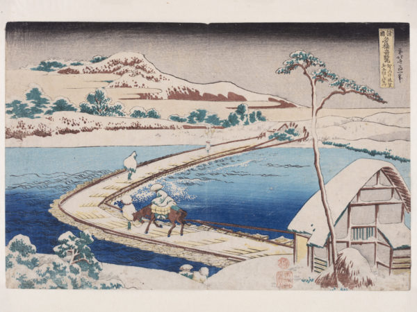 Japanese print of a landscape. a pontoon bridge crosses the marshes. Travellers cross the bridge, one riding a horse, others walking. In the foreground is a building and in the background a mountain rises up.