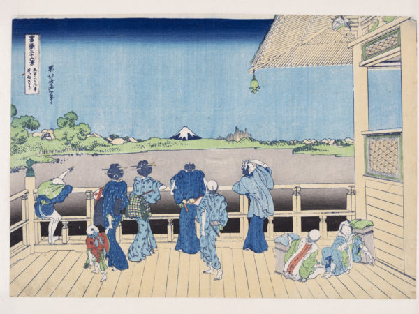 Japanese print of a group of people in elaborate traditional robes standing on a veranda looking out over the landscape. One of the porters points out Mount Fuji in the distance to them. Other porters sit on the floor resting the heavy boxes.