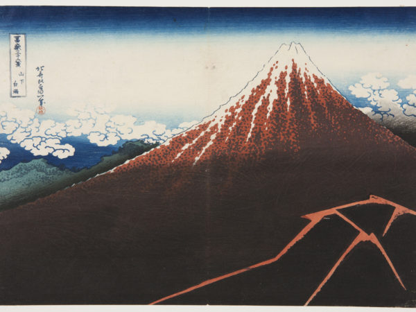 Japanese print of Mount Fuji, dramatic in dark red, snow at the summit and fluffy clouds surrounding it.
