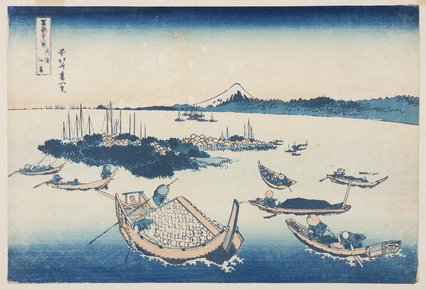 Japanese print of a seascape. Boats sail on the water. A wooded island in the middle with many small buildings. On the horizon Mount Fuji rises up from the shoreline.