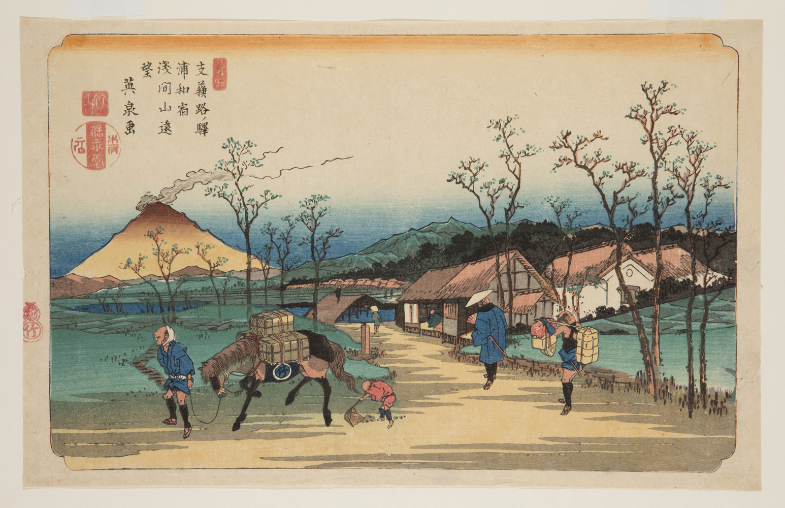 Japanese print of a road, leading to a village and in the distance are mountains. In the foreground are travelers. A man leads a horse carrying boxes, a small figure follows behind scooping up horse manure. A man walks towards the village with an attendant, carrying parcels, following behind.