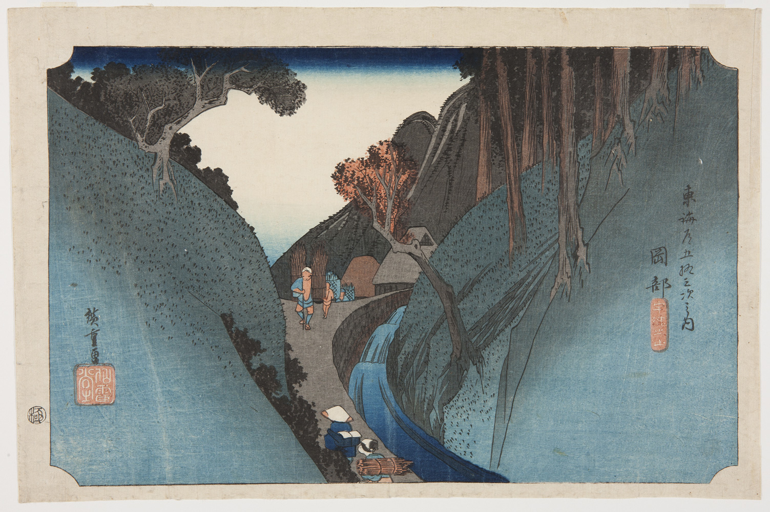 japanese print of a beautiful blue scene of a view through mountains, showing travelers walking up a very steep path and a waterfall next to the path