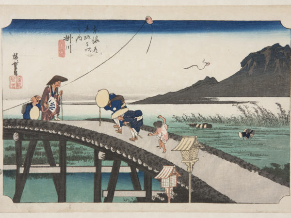japanese print of people in traditional japanese dress walking over a wooden brige. in the background people pick rice in rice fields in front of a mountain