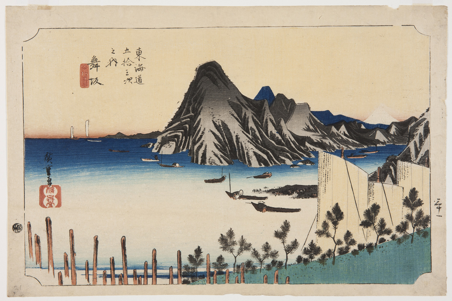 A Japanese print of a landscpe. Small boats on the water with mountainous land in the background.