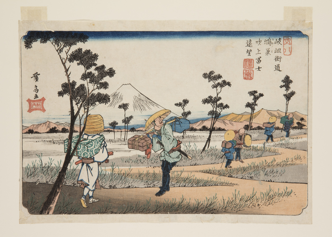 Japanese print of a landscape. A path weaves through fields, mountains in the background. Travelers, dressed in traditional clothes carrying bundles, walk along the path.