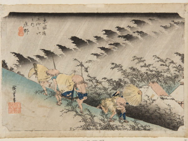 Japanese print. Travelers walk along a hillside dressed in traditional clothes. Two carry a passenger on a chair. They are bent against the weather and the rain slants across the scene top right to bottom left.