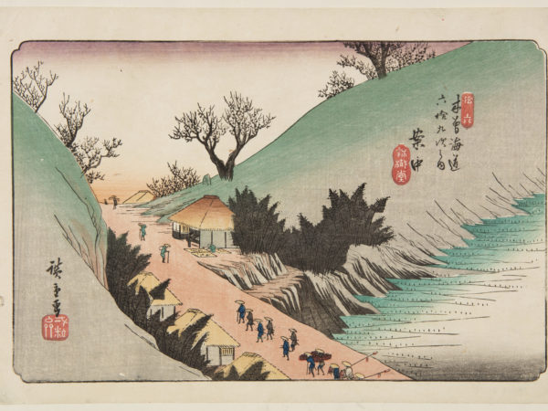 Japanese print of a mountain road. Travelers walk along the road, in traditional clothes. The road has small buildings either side.