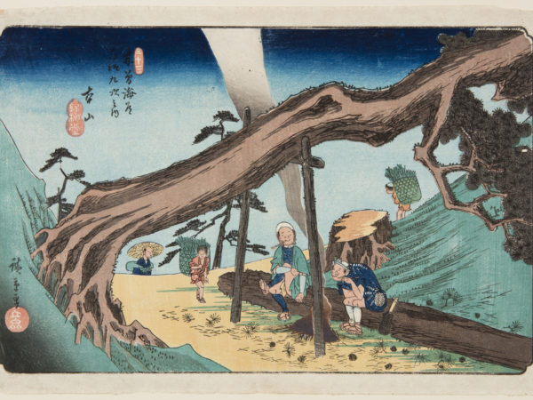 Japanese print of a mountain road. A fallen tree is held up with posts and underneath two men have made a campfire and sit on a fallen log. Three other figures walk along the road carrying large baskets on their back.