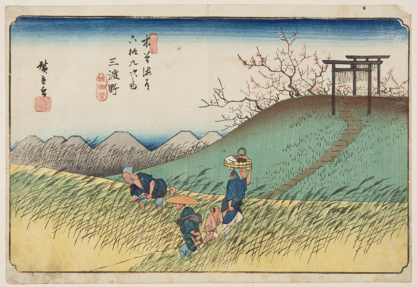 Japanese print of a rural landscape. Four figures dressed in traditional clothes, one bent over tending the fields, another standing, a woman carries a basket on her head and holds a child's hand. A path weaves away over a hill, there is blossom in the trees.