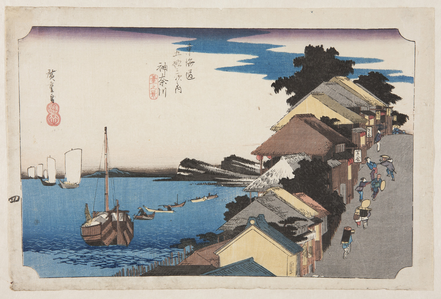 Japanese print of a seaside town. To the left are boats sailing on the water. To the right a street with buildings stretches up the hill. People dressed in traditional clothes walk along the street and women encourage the travellers to come into their inns.