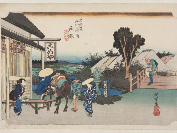 Japanese print of travellers outside an inn. A man, foot in stirrup, prepares to mount a horse, an attendant stands at the side. Two women in elaborate traditional dress look on. A man carrying a box walks down the steps towards the group. In the background are more buildings and countryside beyond.