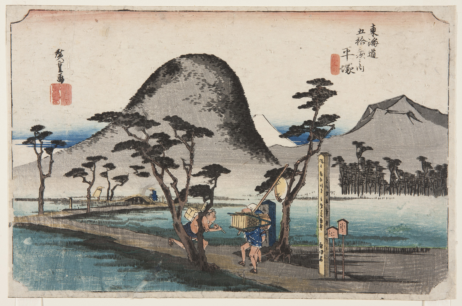 japanese print of a road zig-zagging through a marshy area. on the road a delivery man carrying a box on his back runs past two walking travellers