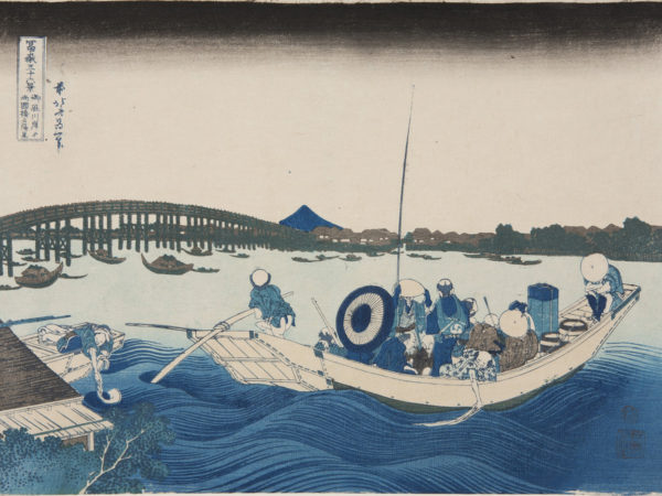 Japanese print of a river scene. In the foreground there are waves and a boat full of passengers, the boatman steers with a pole. Many boats are on the water and a bridge spans the river. The far bank has buildings and trees and Mount Fuji is in the distance.