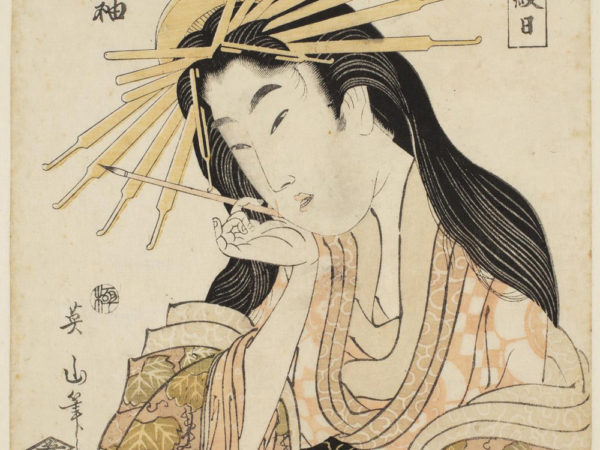Japanese print of a woman dressed in traditional robes. She holds a brush in one hand up by her face and looks down at the piece of paper she holds in the other hand.