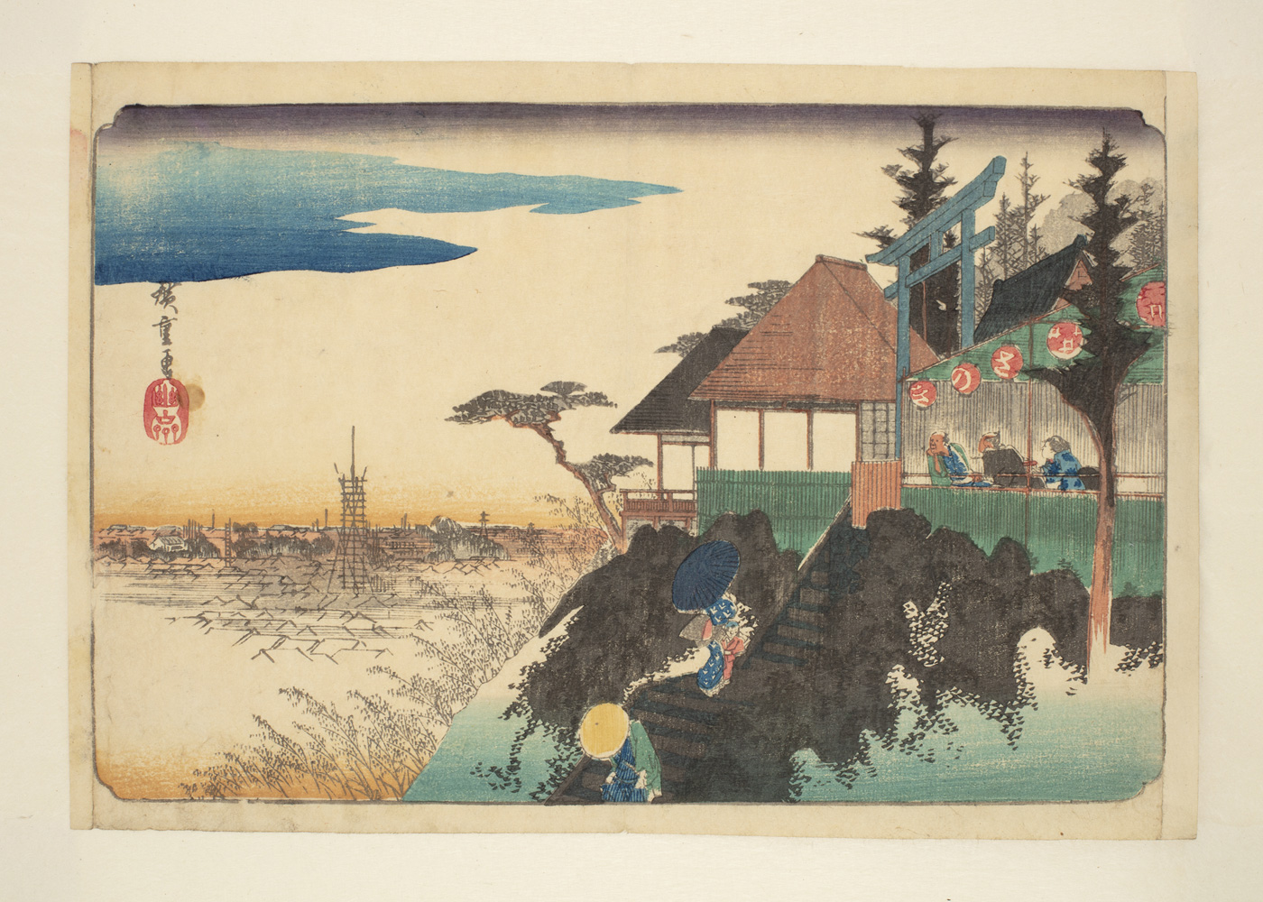 Japanese print. In the foreground two figures climb the steep steps to a building with a balcony where two people are waiting. They are dressed in traditional robes and each carries an umbrella. From this vantage point they can see the landscape below and a distant town.