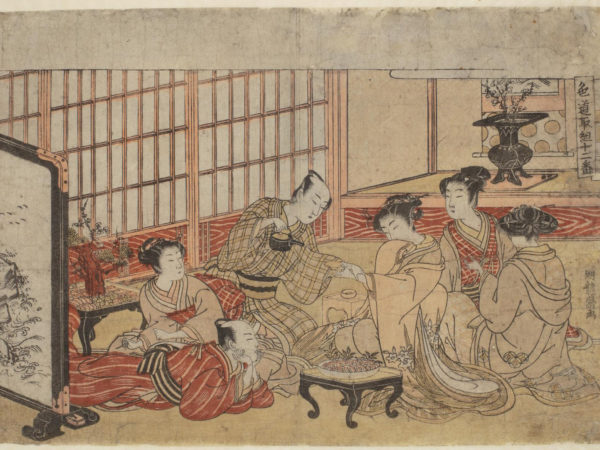 Japanese print of a group of people dressed in traditional clothes seated around a table in a luxurious room. One man is reclining and a woman sits behind him. Another man holds a woman's hand whilst pouring tea, two other women look on.