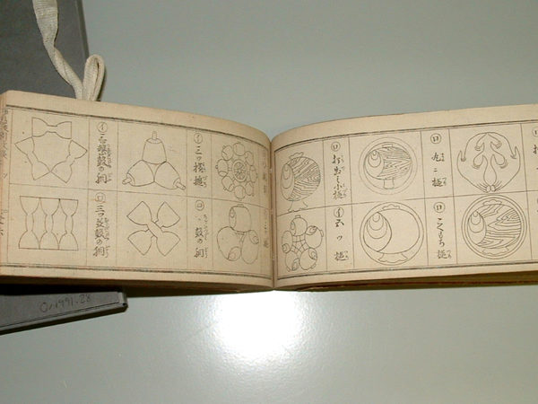 An open book shows line drawings of Japanese family crests, six on each page, and Japanese text.