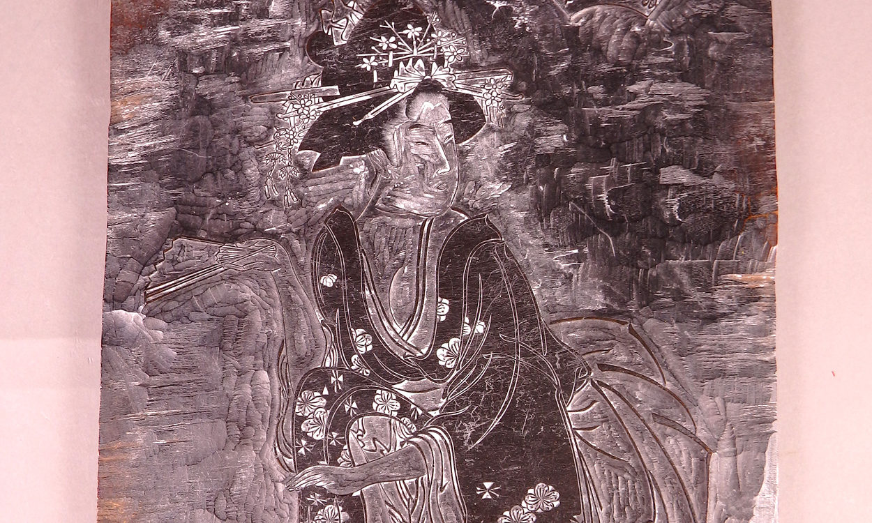 A japanese woodblock with an image of a woman, seated, dressed in traditional clothes.