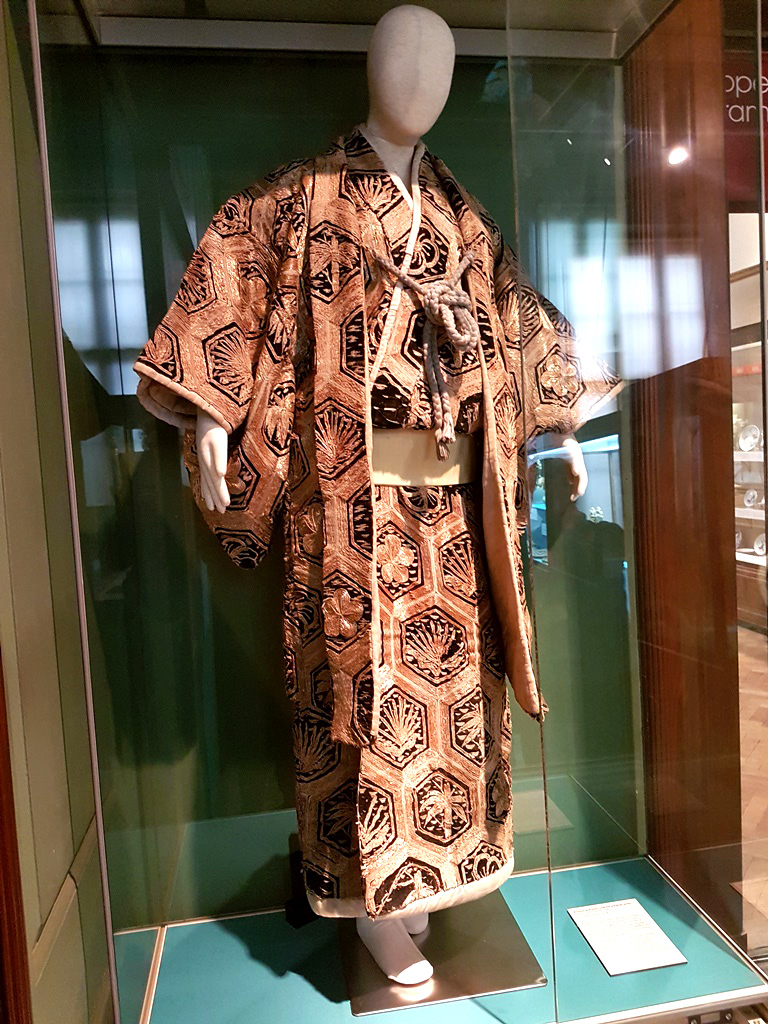 A mannequin in a glass display cabinet dressed in a kimono with a hexagon motif.